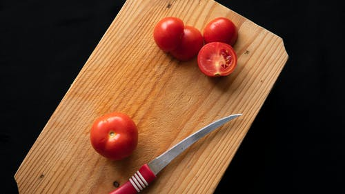 Wooden board with ripe tomatoes and knife