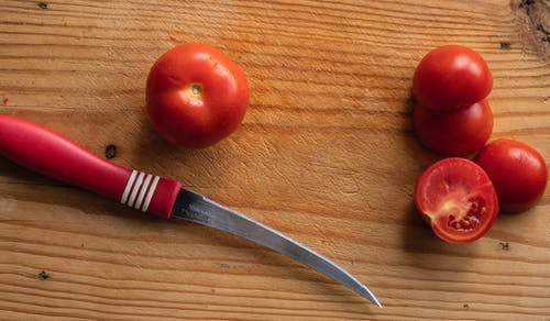 Knife with fresh tomatoes on wooden board