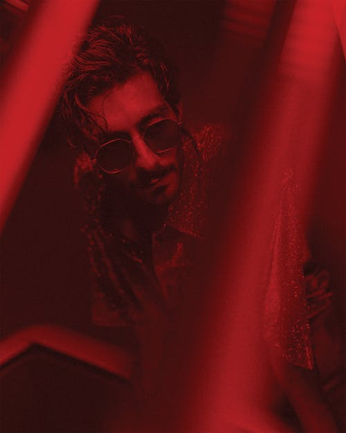 High angle of handsome male with beard and hairstyle in sunglasses standing under red illumination