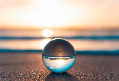 Blue and Silver Ball on Brown Sand