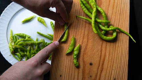 From above hands of crop unrecognizable person cutting hot peppers on cutting board and putting slices on plate