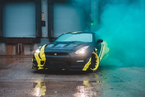 Modern stylish automobile with glowing headlights on wet asphalt surface in vibrant smoke