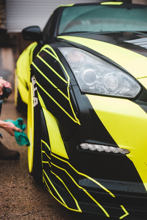 Crop faceless person cleaning sport automobile with stylish design of body and expressive headlights