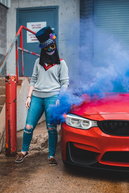 Full body of anonymous female wearing scary mask and black hat standing near red automobile and metal railing with blue smoke grenade in hand