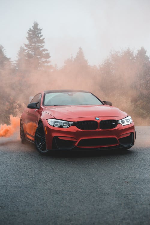 Bright modern car covered with colorful smoke on asphalt road against green trees