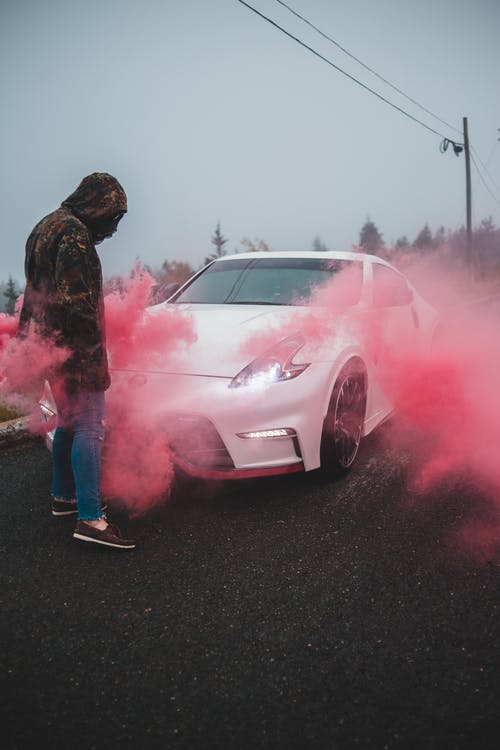 Woman standing near shiny car covered in colored smoke