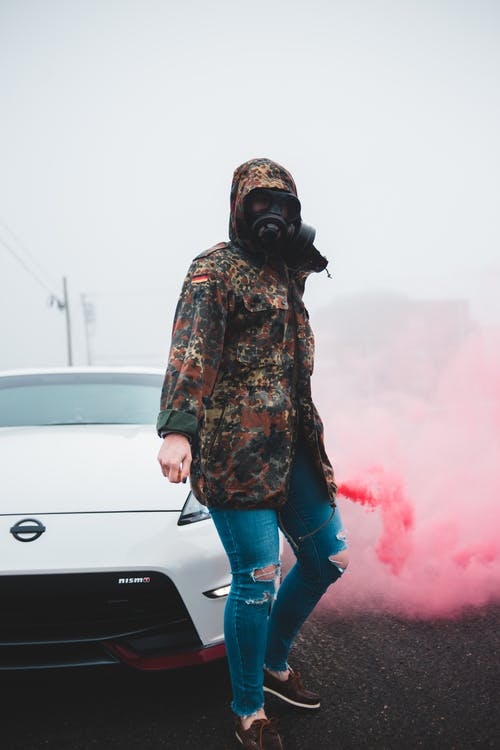 Full body of anonymous young female in gas mask spreading colored smoke while standing near luxury vehicle in mist