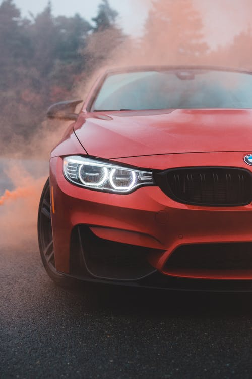Red car with shiny headlights in colored smoke