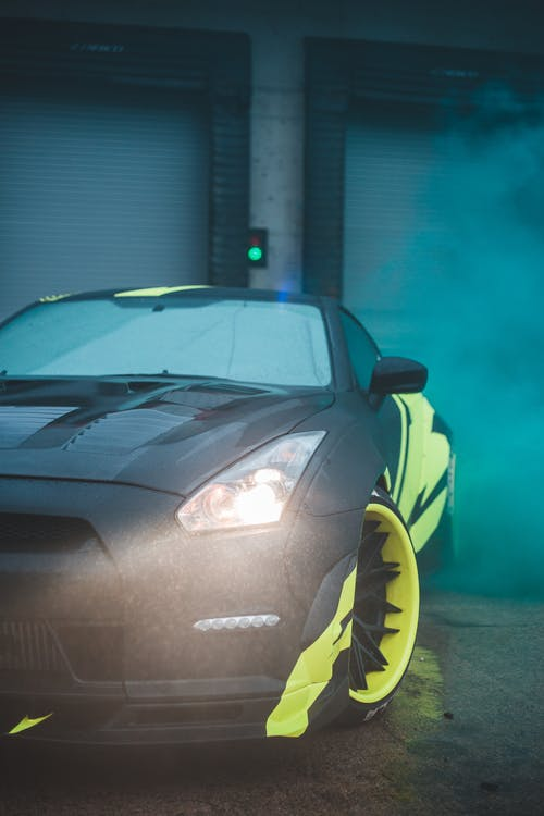 Contemporary black sports car with yellow wrapping decal design and headlight light parked on street with fume from smoke bomb near closed blinds
