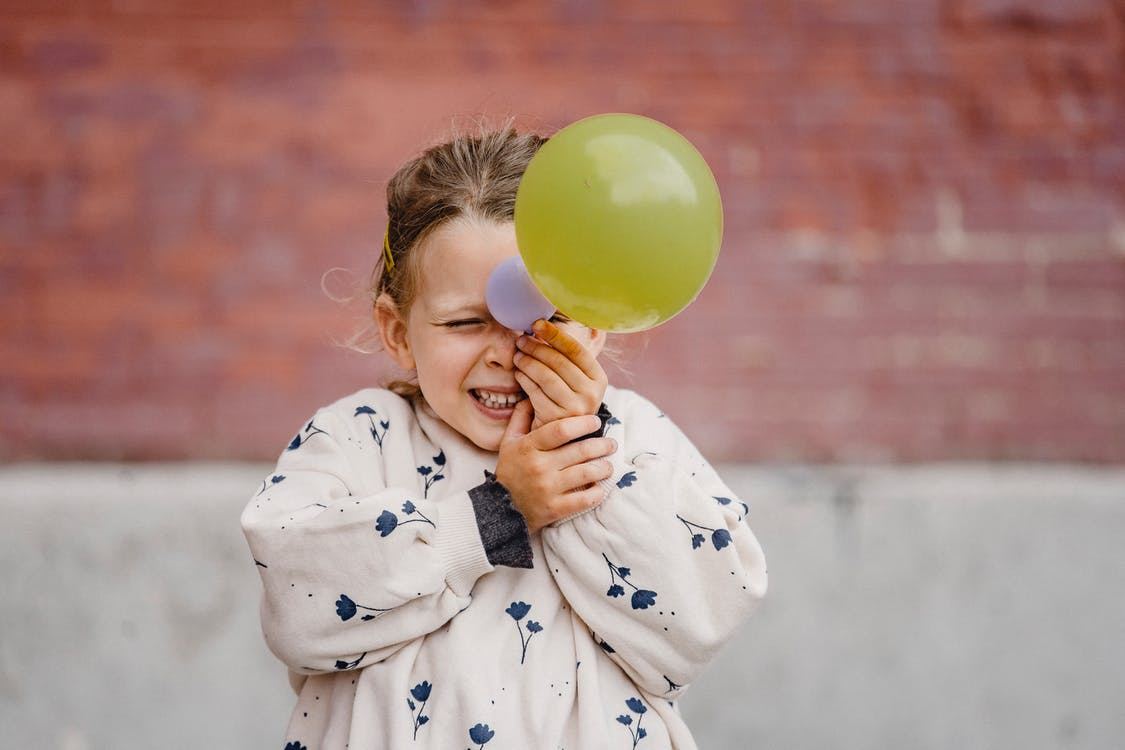 Happy playful girl with balloon near building