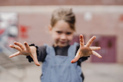 Adorable little girl in casual clothes with painted fingers outstretching arms towards camera while drawing in kindergarten