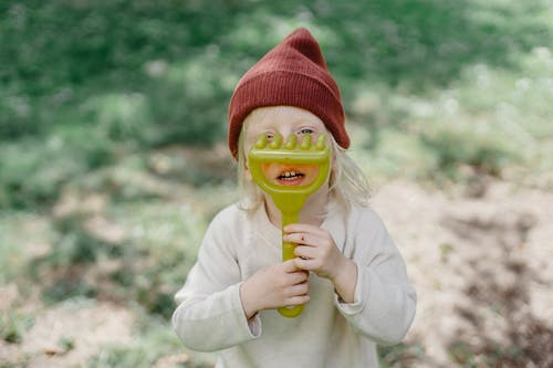 Girl in White Sweater Holding Green and Yellow Plastic Toy