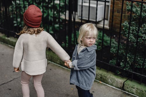 Meisje In Grijze Trui En Blauwe Rok Staande Op Grijze Betonnen Stoep