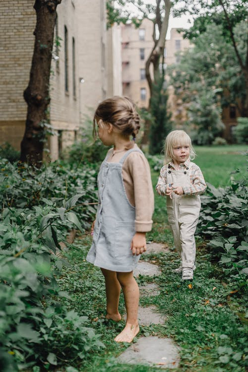 Meisje In Roze Shirt Met Lange Mouwen En Witte Rok Staande Op Groen Gras