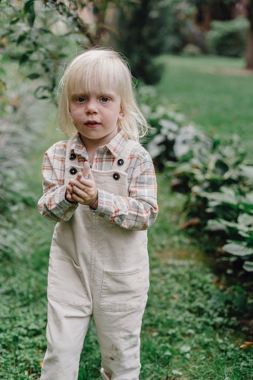 Cute little girl standing on grass in park