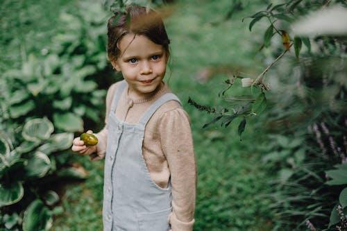 Cute little girl standing in verdant garden