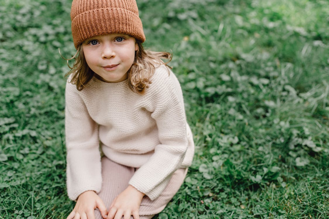 Girl in White Sweater and Brown Knit Cap Sitting on Green Grass