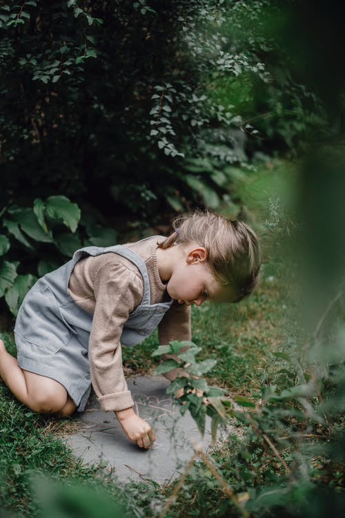 Boy in Gray Long Sleeve Shirt and Gray Shorts Sitting on Green Grass