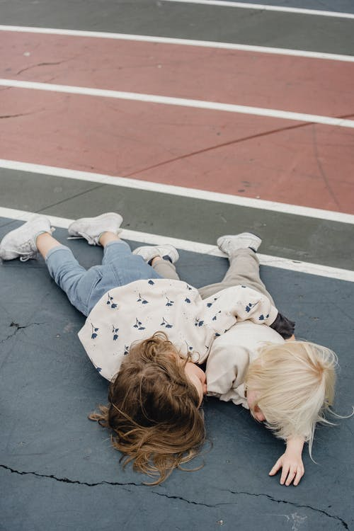 Cute girls lying on sports ground together