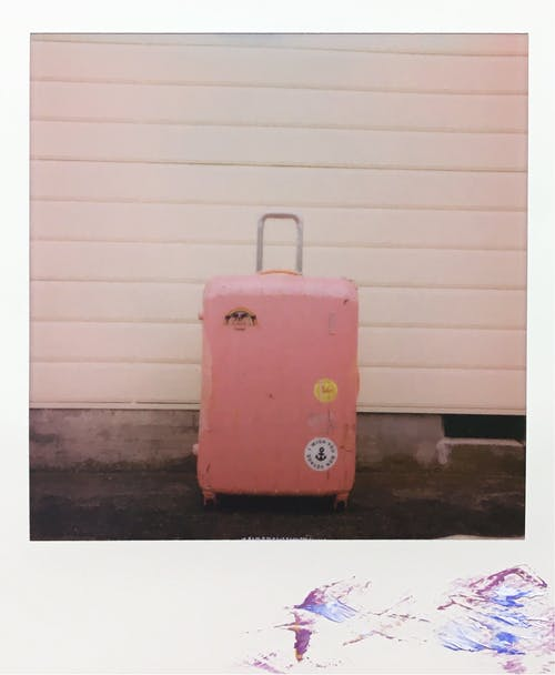 Pink Luggage Bag on White Wooden Wall