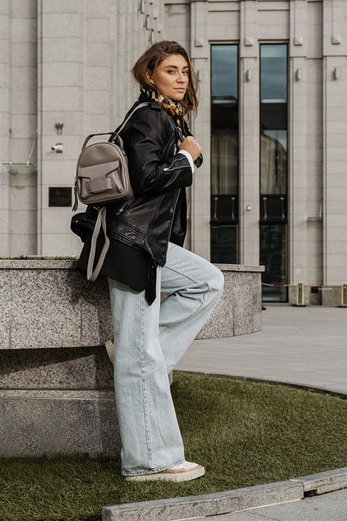Woman in Black Leather Jacket and Gray Pants With Black Leather Backpack Standing on Sidewalk during