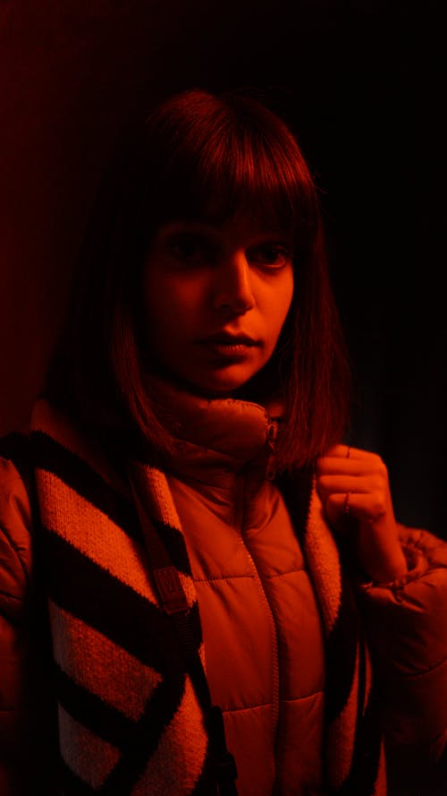Thoughtful woman in warm jacket in red light