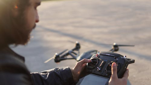 From above of crop bearded male operator controlling drone with remote control with display at daytime