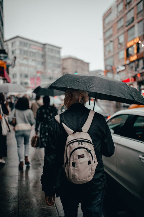 Faceless tourist with umbrella in city