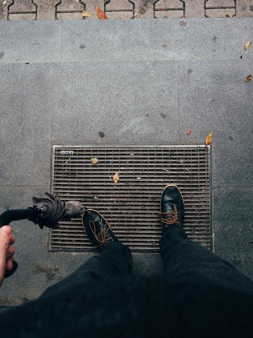 Crop man in dark shoes with umbrella
