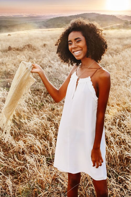 Woman in White Spaghetti Strap Dress Standing on Brown Grass Field