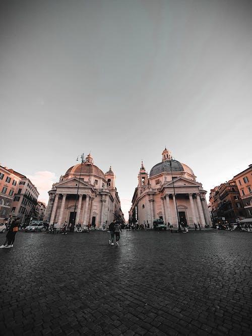 Low angle of tourist walking on square Piazza del Popolo with Santa Maria dei Miracoli and Santa Maria di Montesanto churches in Rome