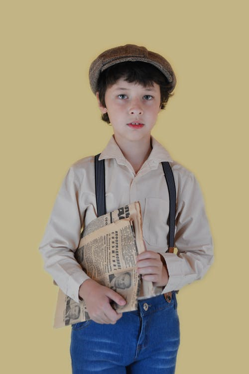 Pensive boy in old fashioned clothes standing with newspaper and looking at camera against yellow background