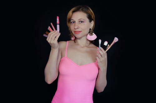 Cheerful woman makeup artist in pink top demonstrating different beauty products and cosmetic brushes and looking at camera against black background