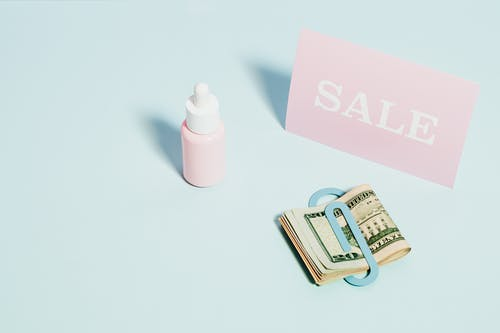 Pink And White Plastic Bottle Beside Money