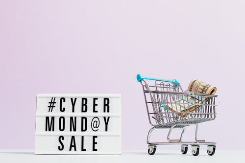TCas Money On A Shopping Cart Beside A Cyber Monday Sale Signext