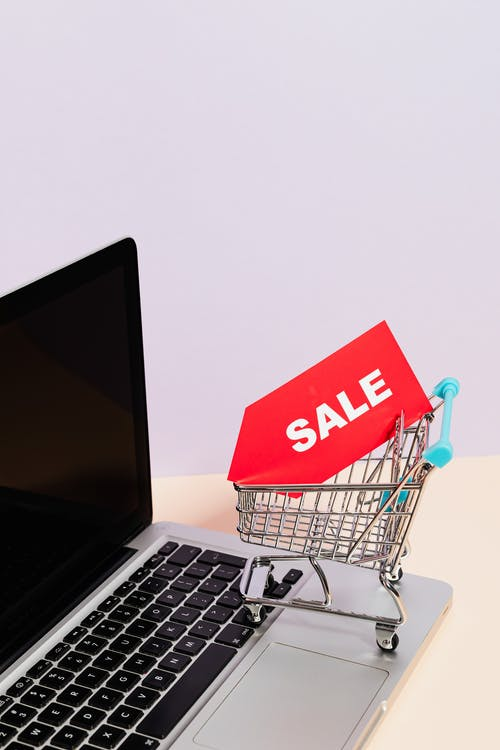 A Red Sale Tag on a Miniature Shopping Cart Placed on a Macbook Laptop