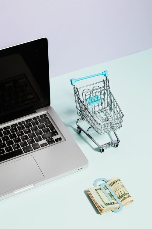 A Macbook Beside a Miniature Shopping Cart and Clipped Money