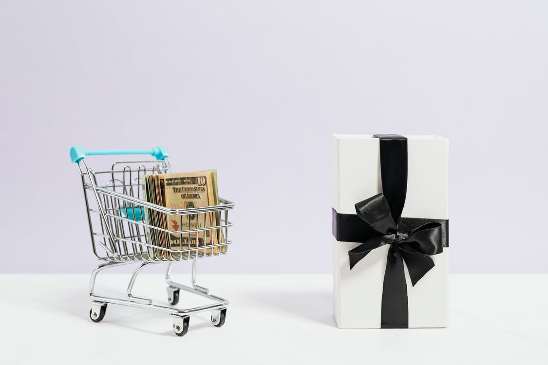 Stainless Steel Shopping Cart Beside A Present
