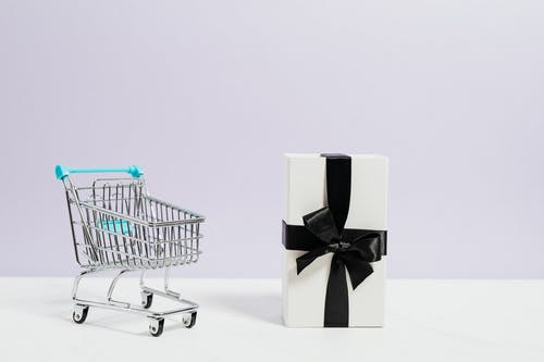 Shopping Cart Next to a Gift Box