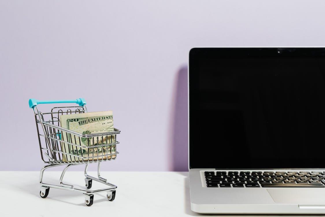Shopping Cart Next to a Laptop