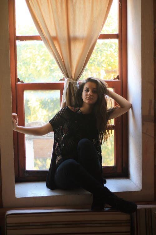 Pensive young female with long brown hair in black clothes sitting on windowsill and touching hair in daytime
