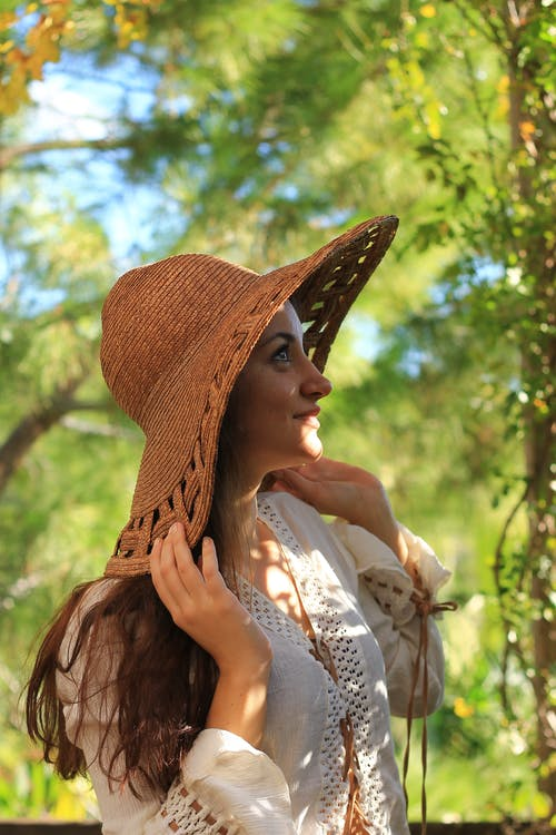 Side view of charming female with long hair in stylish clothes touching hat and standing in green park in sunny day