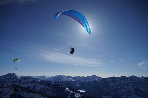Person in Black and Red Parachute over Snow Covered Mountains