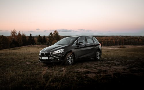 Modern black car parked on grassy meadow in countryside