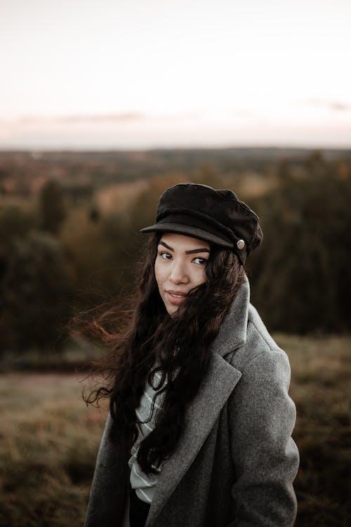 Woman in Gray Coat Standing on Brown Field
