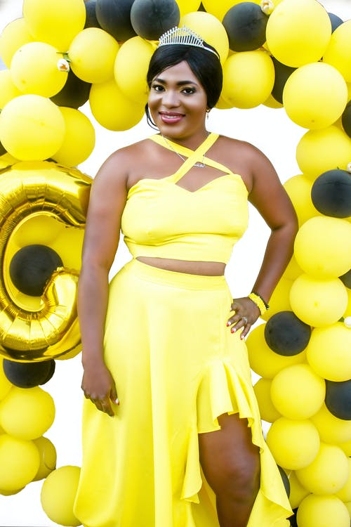 Black happy woman smiling in bright yellow outfit among balloons