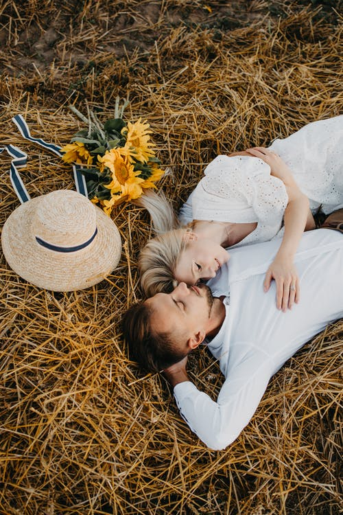 Man in White Shirt Kissing Woman in White Dress on Brown Grass Field