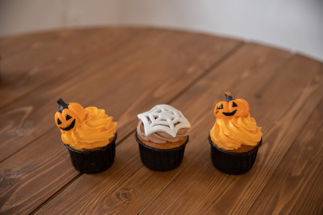 Three Halloween Cupcakes on Brown Wooden Table