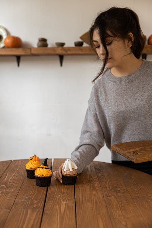 Woman in Gray Sweater Holding A Ghost Cupcake On The Table