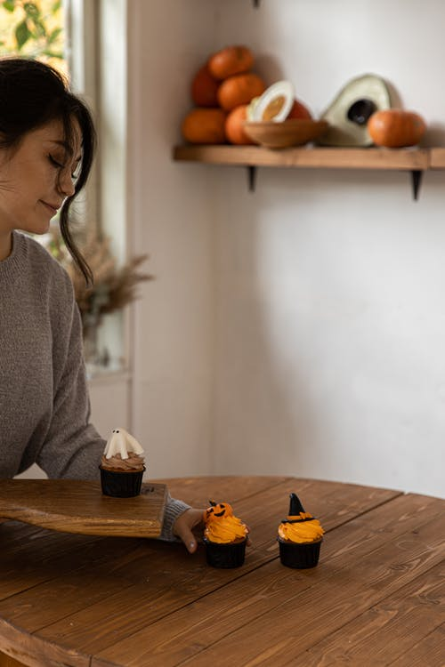 Woman Putting Cupcakes On A Wooden Board